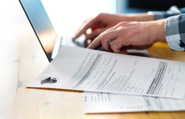 Acceso Universidad. Portátil unas manos trabajando sobre él y documentación..