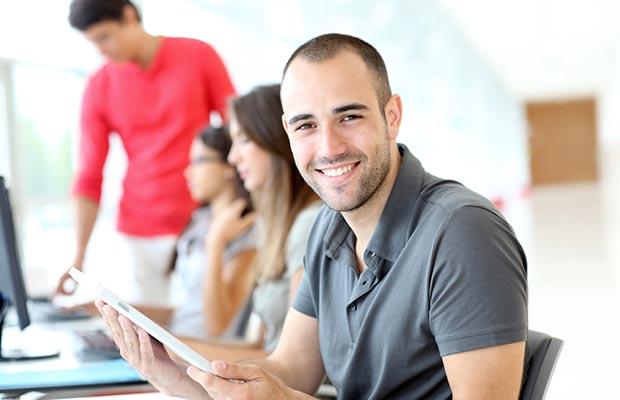 Grado en Ingeniería Informática. Grupo de jovenes trabajando en linea mirando pantallas de ordenador, en primer plano joven sonriendo.