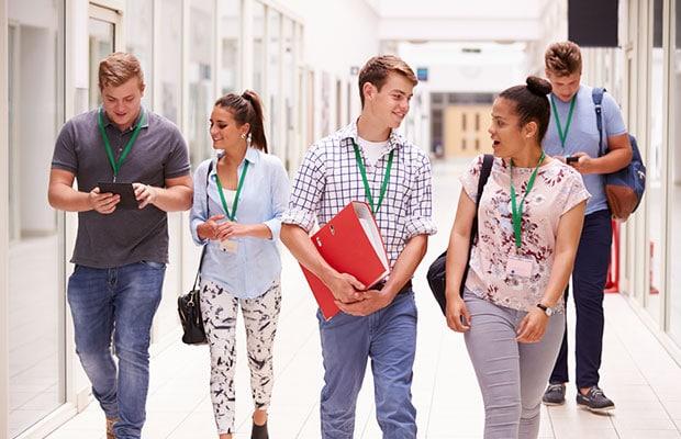 Carne estudiantes. Estudiantes en pareja andando y charlando, con identificador colgado.