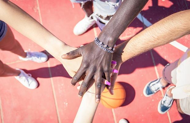 Superposición de manos, distinta piel, genero, fondo de la imágen balon de baloncesto.
