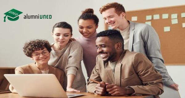 Grupo de jóvenes juntos visualizando algo en un portátil sonriendo.