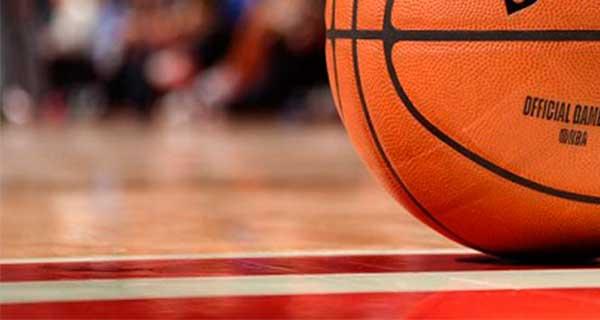 Sobre una pista de baloncesto, imagen en primer plano de un balón de baloncesto.