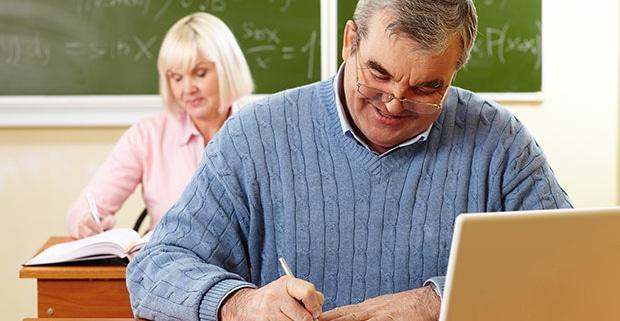 Dos alumnos de SENIOR en un aula uno de ellos con un portátil.