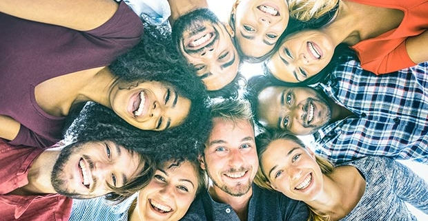 Grupo de jovenes imágen de sus caras todas formando un circulo.